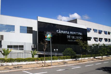 """#PraCegoVer: Foto mostra a fachada da Câmara. Em uma estrutura com revestimento preto está escrito """"Câmara Municipal de Valinhos"""" e ao lado está o brasão do município."""