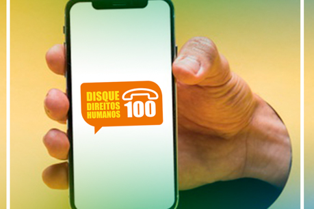 """#PraCegoVer: Foto mostra mão segurando um celular. Na tela está escrito: """"Disque Direitos Humanos - 100""""."""