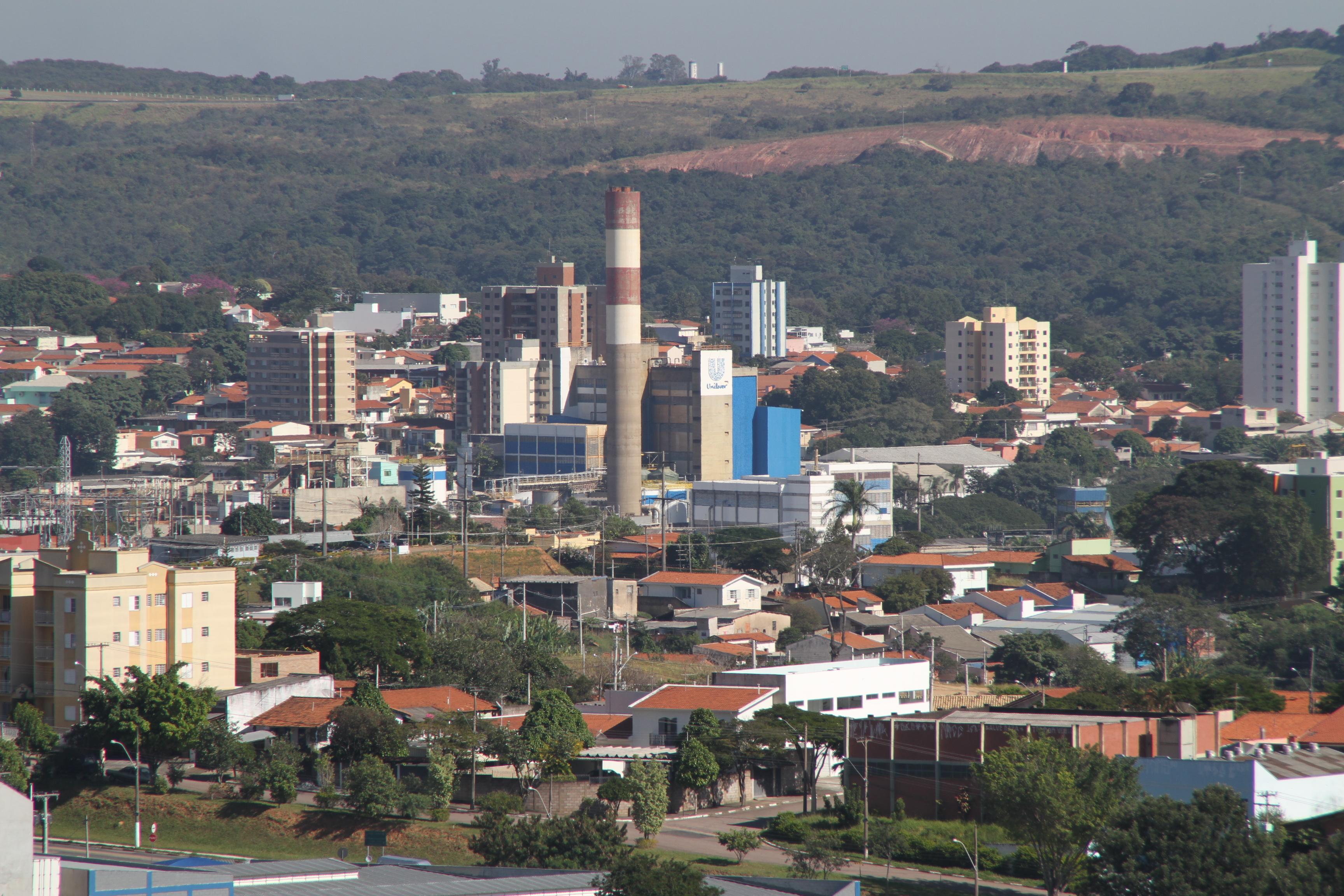 #PraCegoVer: Vista de área central de Valinhos. No primeiro plano da foto, vêem-se casas e edifícios baixos; no meio, uma fábrica com chaminé; ao fundo, morros cobertos com vegetação, ou desmatados.