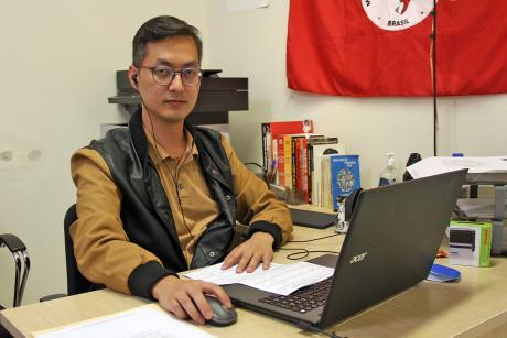 #PraCegoVer:  Vereador Marcelo Yoshida olha para a câmera em sentado a uma mesa, de onde acompanha a sessão em seu computador portátil. Ao fundo veem-se livros, uma impressora e parte de uma bandeira vermelha.