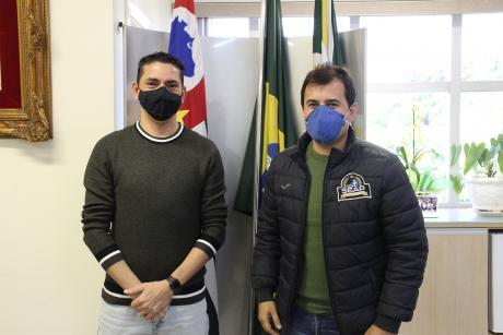 #PraCegoVer: Foto mostra o presidente Franklin e o proprietário da VV8, Juninho da Seap, em pé, posando para a foto em frente às bandeiras do estado, do Brasil e do município, no Gabinete da Presidência. Ambos usam máscara.