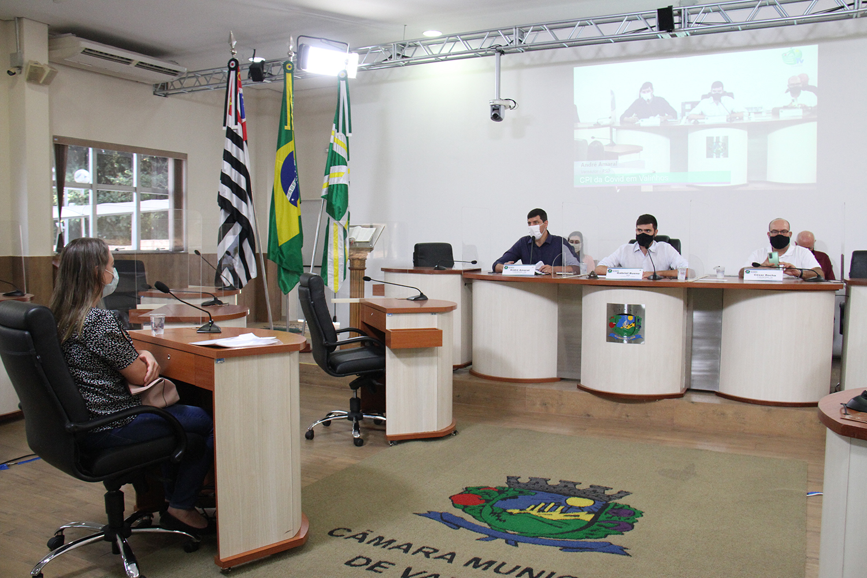 #PraCegoVer: Foto mostra Vânia Peretti sentada no plenário da Câmara, ouvindo as perguntas do vereador Gabriel Bueno. Ao lado de Gabriel, estão os vereadores André Amaral à direita e César Rocha à esquerda.