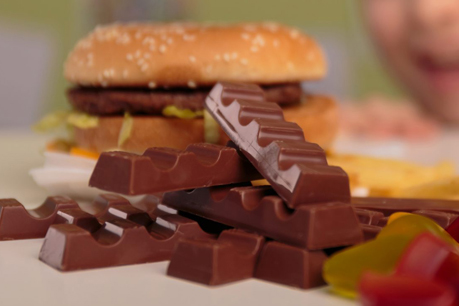 #PraCegoVer: foto mostra alimentos industrializados como chocolate e sanduíche. Ao fundo, em desfoque, há uma criança olhando para a comida.