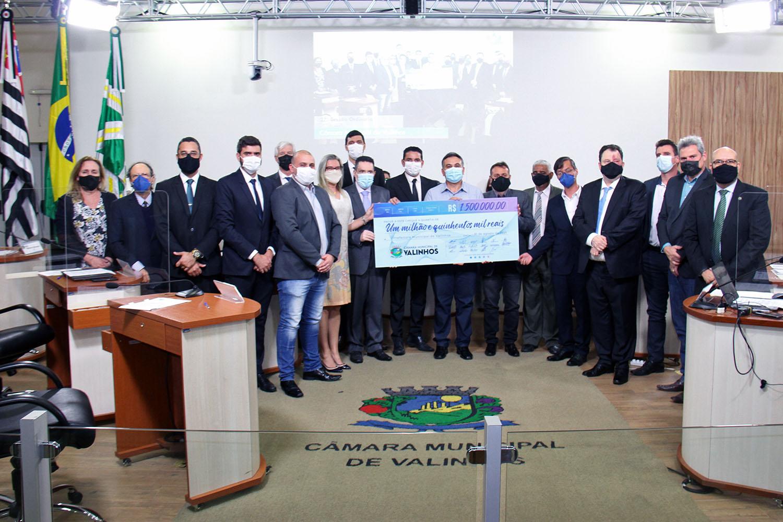 #PraCegoVer: Vereadores em semicírculo posam para foto no plenário da Câmara. No centro, o vice-prefeito, Major Rocco (PSD), segura um cheque gigante, com o valor de R$ 1,5 mi.