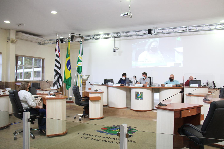 #PraCegoVer: Foto mostra os vereadores Gabriel Bueno, Rodrigo Toloi e César Rocha sentados na mesa principal do plenário, ouvindo a ex-diretora Ana Maria Desti Júlio.