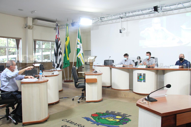 #PraCegoVer: Foto mostra o ex-secretário da Saúde Luiz Carlos Fustinoni prestando depoimento aos vereadores Gabriel Bueno, Rodrigo Toloi e César Rocha. Ele está sentado no plenário de frente para os vereadores, que também estão sentados.