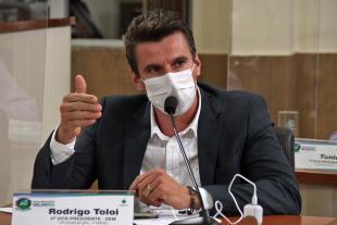#PraCegoVer: Foto mostra o vereador Rodrigo Toloi sentado em seu lugar no plenário, discursando durante a sessão.
